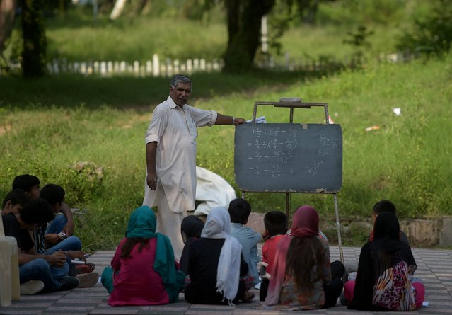 """In this photograph taken on August 30, 2016, Muhammad Ayub, an employee with Pakistan's Civil Defence service, teaches pupils at a makeshift school in a park in Islamabad. In the corner of a pristine park in one of Islamabad's poshest areas, an open-air classroom run by an aging rescue-worker offers a beacon of hope to the city's poorest residents. For the past 30 years, """"Master"""" Muhammad Ayub, whose day job includes defusing bombs and putting out fires, has cycled from his office to the makeshift school to teach children from surrounding slums for free. (Photo by Aamir Qureshi/AFP Photo)"""