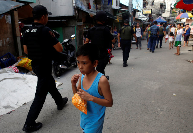 A boy holds snacks in a plastic bag as he walks past policemen conducting anti-drugs operation in Mandaluyong, Metro Manila in the Philippines, November 10, 2016. (Photo by Erik De Castro/Reuters)