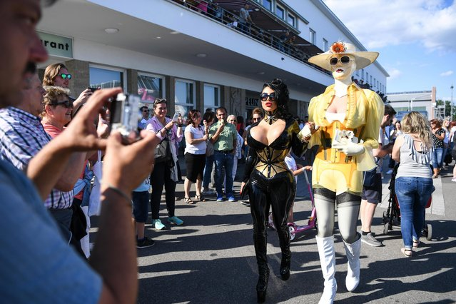 """Participants of the """"Torture Ships"""" walk to the pier where the Ship of lacquer and leather will undock with hundreds watching in Friedrichshafen, Germany on June 23, 2018. Filled with scantily-clad woman and leather-bound men, the boat docked in the city of Konstanz on Sunday morning. The huge barge has been ferrying bondage enthusiasts around the lake for 22 years. BDSM stands for Bondage and Discipline, Dominance and Submission, and Sadism and Masochism. Astonishing pictures show fetish-lovers lining up for their place on the naughty ship. (Photo by Felix Kästle/DPA)"""