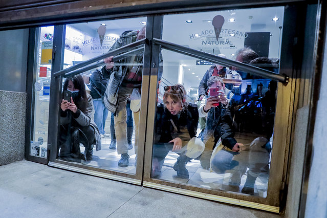 People stand inside of a coffee bar during clash with police and demonstrators following a protest condemning the arrest of rap singer Pablo Hasel in Madrid, Spain, Wednesday, February 17, 2021. (Photo by Manu Fernandez/AP Photo)