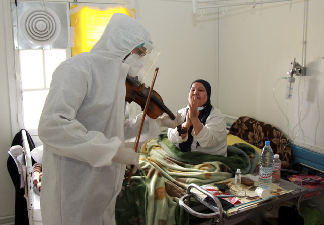 Dr. Mohamed Salah Siala plays the violin for patients on the COVID wards of the Hedi Chaker hospital in Sfax, eastern Tunisia, Saturday February 20, 2021. When the 25-year-old decided to get out his violin one day at Hedi Chaker Hospital in city of Sfax and play, it won praise for boosting the morale of virus sufferers who remained isolated and needed a smile. (Photo by AP Photo/Stringer)