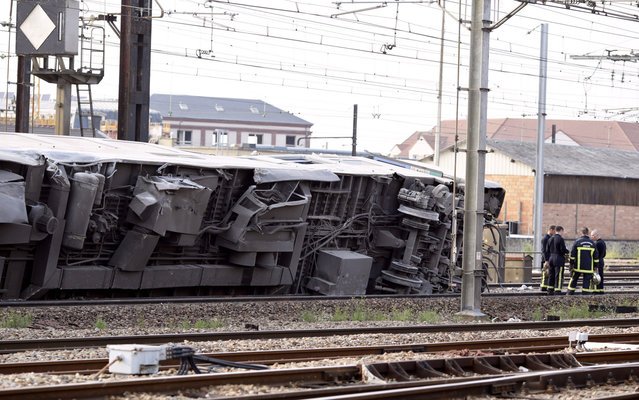 "A picture shows a derailed wagon on the site of a train accident in the railway station of Bretigny-sur-Orge on July 12, 2013 near Paris. A train derailed in the Paris suburb of Bretigny-sur-Orge in an accident that caused ""many casualties"", authorities said. (Photo by Kenzo Tribouillard/AFP Photo)"