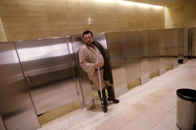"""A man dressed as a character from Star Wars exits the bathroom during an event held for the release of the film """"Star Wars: The Force Awakens"""" at a movie theater in Guatemala City, December 16, 2015. (Photo by Jorge Dan Lopez/Reuters)"""