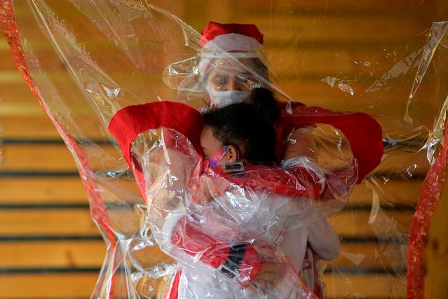 Volunteer Fatima Sanson, dressed up as Mrs. Claus, embraces a needy child in Belo Horizonte, Minas Gerais state, Brazil on December 7, 2020. Fatima Sanson delivers gifts and hugs to needy children every Christmas, but due to the coronavirus pandemic, this year she built an embrace curtain to allow children to touch her, keeping everyone safe. (Photo by Douglas Magno/AFP Photo)