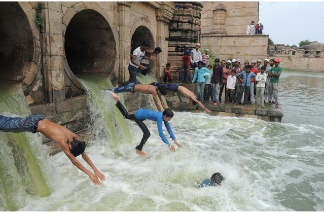 """Indian Muslim youth dive as flood waters enter the tank of the 600 year old Sarkhej Roza architectural complex, which has been dry for the last seven years, in Ahmedabad on July 14, 2013. The Sarkhej Roza is maintained by the Archeological Survey of India and this tomb and mosque of a Sufi saint are known in this region as """"Ganj Bakhsh"""". (Photo by Sam Panthaky/AFP Photo)"""