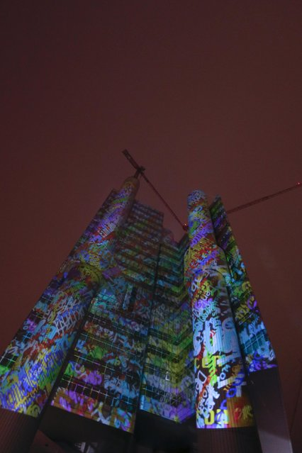 "The HVB banking tower of the German HypoVereinsbank is illuminated with the title ""Green Building"" by German artist Philipp Geist in Munich, January 23, 2015. The installation with the motto ""HVB – The Tower to inspire"" is part of the Munich's ""long night of architecture"" festival and runs seven days. (Photo by Michael Dalder/Reuters)"