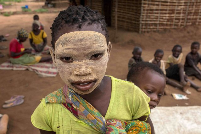 A young girl from the Makonde ethnic group wearing earth makeup on her facen, a beauty symbol, carries a baby on her back as she poses for pictures in the community of Marupa, a relocation center for internally displaced families in the Chiure district, on February 23, 2021. Thousands of families from different districts of the Cabo Delgado province who have been displaced have been located by the government in different areas of the province. (Photo by Alfredo Zuniga/AFP Photo)