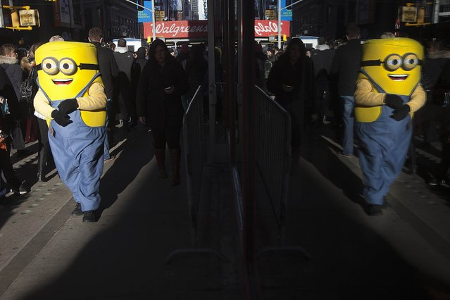 A person dressed up as a Minion is reflected in a window at Times Sqaure in New York December 29, 2014. (Photo by Carlo Allegri/Reuters)