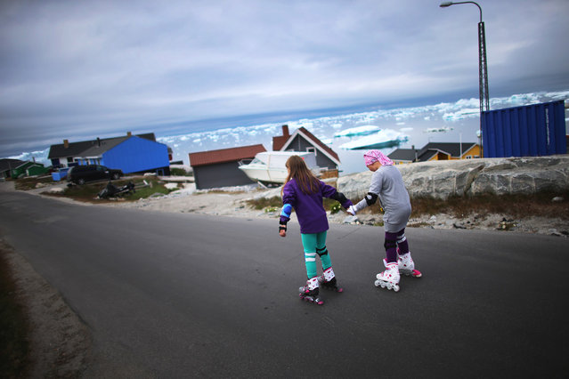Youngsters rollerblade on an Ilulissat street in Greenland, on July 18, 2013. (Photo by Joe Raedle/Getty Images via The Atlantic)