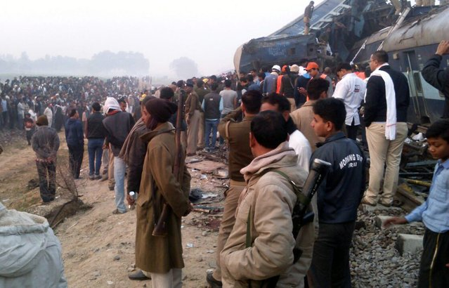 People gather at the spot as rescue works continue at the site of an accident where coaches of an Indore-Patna Express train derailed off the tracks, near Pukhrayan area, in Kanpur, India, 20 November 2016. According to reports, over 60 people were killed and more than 100 were injured after 14 coaches of an Indore-Patna Express train derailed in the early morning hours. (Photo by Ritesh Shukla/EPA)