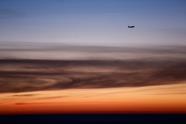 A plane prepares to land at Barcelona airport as the sun rises on December 31, 2017. (Photo by Pau Barrena/AFP Photo)