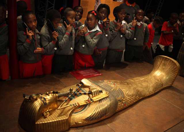 """In this photo taken Wednesday, January 28, 2015, schoolchildren roam an exhibition of  replicas of Tutankhamun's treasures at an exhibition at a Krugersdorp, South Africa, Casino, brought to South Africa by Egypt's former top antiquities official Zahi Hawass. In an interview with the Associated Press, Hawass declared that """"Egypt is safe"""" adding that antiquities sites are safe. (Photo by Denis Farrell/AP Photo)"""