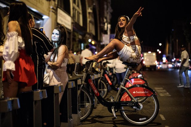 A reveller perches on a public hire bicycle outside a bar in Shoreditch, the weekend before new licensing rules come in to effect across Hackney on July 28, 2018 in London, England. (Photo by Jack Taylor/Getty Images)