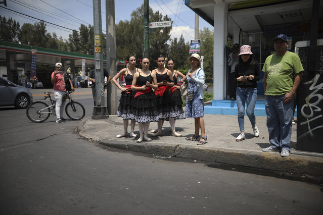 Ballet dancers wait on a  street corner as they wait to perform, in Mexico City, Saturday, July 28, 2018. (Photo by Emilio Espejel/AP Photo)