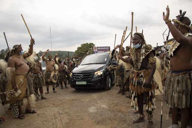 """Amabutho (Zulu regiments) form a guard of honour as they escort a hearse carrying the body of King Goodwill Zwelithini from a mortuary in Nongoma, KwaZulu Natal on March 17, 2021. King Goodwill Zwelithini died on March 12, 2021 in the eastern city of Durban, aged 72, after weeks of treatment for a diabetes-related illness. His remains have been taken back to his birthplace, the small southeastern town of Nongoma in Kwa-Zulu Natal province, where he will be laid to rest after midnight. The intimate ceremony, to be conducted behind closed doors at the KwaKhethomthandayo royal residence, is referred to as a """"planting"""" rather than a burial. (Photo by Phill Magakoe/AFP Photo)"""