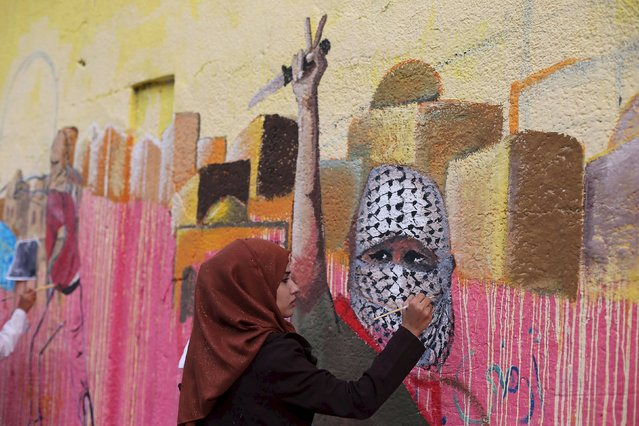 A Palestinian woman paints a mural, depicting a masked Palestinian holding a knife, in support of Palestinians committing stabbing attacks against Israelis, in Rafah in the southern Gaza Strip November 3, 2015. (Photo by Ibraheem Abu Mustafa/Reuters)