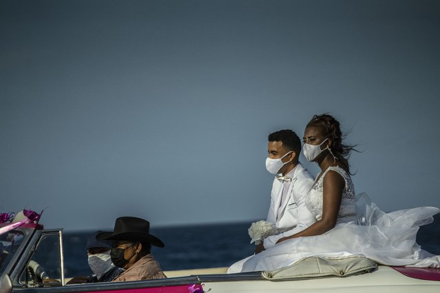 Wearing masks against the spread of the new coronavirus, a newly married couple takes a ride on a classic American car along the Malecon in Havana, Cuba, Thursday, February 11, 2021. (Photo by Ramon Espinosa/AP Photo)