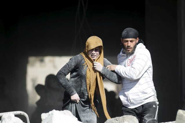 A man helps an injured woman in a site hit by what activists said were airstrikes carried out by the Russian air force in the rebel-controlled area of Maaret al-Numan town in Idlib province, Syria January 9, 2016. (Photo by Khalil Ashawi/Reuters)