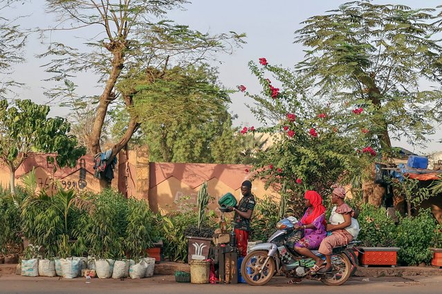 Two women on motorcycle a street of Bamako, Mali on April 13, 2021. Among the 25 poorest countries in the world, Mali depends on gold mining and agricultural exports. (Photo by Mehmet Kaman/Anadolu Agency via Getty Images)