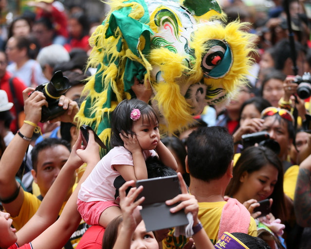 A girl covers her ears during the noisy celebration of the Chinese New Year at Manila's Chinatown district of Binondo Thursday, February 19, 2015 in Manila, Philippines. (Photo by Bullit Marquez/AP Photo)
