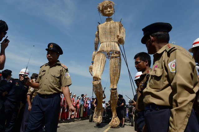 Myanmar civil security personnel escort an eight-metre tall wicker puppet from the French cultural group L'Homme Debout during a parade in Yangon city's Dala township on December 2, 2016 to mark the opening of the Mingalabar Festival. (Photo by Romeo Gacad/AFP Photo)