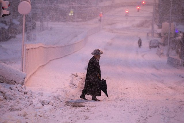An ultra-Orthodox Jewish man walks on a snow-covered street early morning near Jerusalem's Mea Shearim neighbourhood February 20, 2015. Snow covered Jerusalem and mountainous areas of Israel early Friday morning and the education ministry closed schools for the day. (Photo by Ronen Zvulun/Reuters)