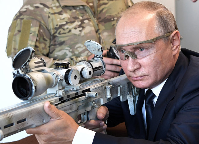 Russian President Vladimir Putin aims a sniper rifle during a visit to the Patriot military exhibition center outside Moscow, Russia, Wednesday, September 19, 2018. Putin chaired a meeting that focused on new arms programs. (Photo by Alexei Nikolsky/Sputnik/Kremlin Pool Photo via AP Photo)