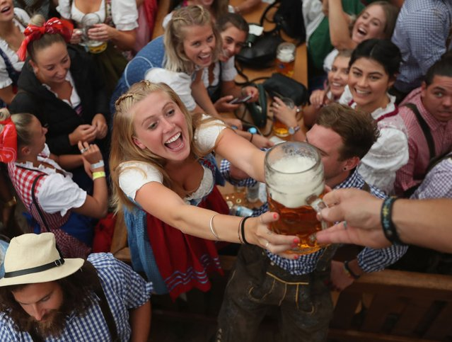 Visitors celebrate in a beer tent at the opening day of the 2018 Oktoberfest beer festival on September 22, 2018 in Munich, Germany. The Oktoberfest lasts until October 7 and is the world's largest beer festival. The beer festival typically draws over six million visitors. (Photo by Alexandra Beier/Getty Images)