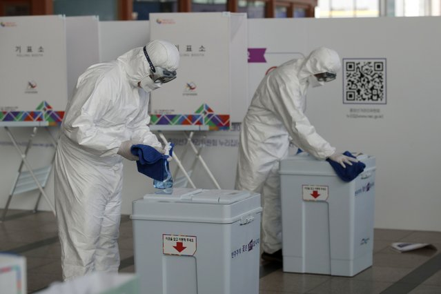 Workers wearing protective gears disinfect as a precaution against the coronavirus ahead of the early voting for the upcoming Seoul mayoral by-election at a local polling station in Seoul, South Korea, Thursday, April 1, 2021. The early voting for the April 7 Seoul and Busan mayoral by-election will be held for two-days on April 2-3. (Photo by Lee Jin-man/AP Photo)