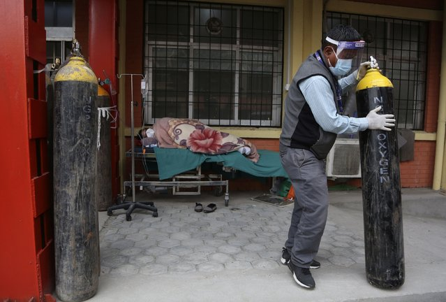 A Nepalese paramedic moves away an empty oxygen cylinder as a COVID-19 patient lies on a bed outside an emergency ward of a government run hospital in Kathmandu, Nepal, Friday, May 7, 2021. (Photo by Niranjan Shrestha/AP Photo)