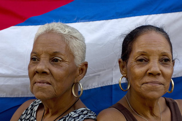 "In this September 29, 2013 photo, 65-year-old twin Fe Fernandez, left, and her sister Esperanza pose for a portrait in front a Cuban flag on their street in Havana, Cuba. Neighbors all marvel at the 12 sets of twins living along two consecutive blocks in western Havana, ranging in age from newborns to senior citizens. ""We were the first ones"", said Fe Fernandez. (Photo by Ramon Espinosa/AP Photo)"