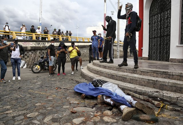 Anti-government protesters stand next to the body of Fredy Bermudez, a man they killed in retaliation for shooting to death two fellow protesters at roadblock set up by the protesters, in Cali, Colombia, Friday, May 28, 2021. Colombia's chief law enforcement Francisco Barbosa confirmed that Bermudez was an official of the Attorney General's office. (Photo by Andres Gonzalez/AP Photo)