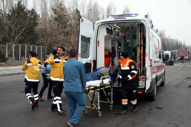 A wounded man is carried to an ambulance after a bus was hit by an explosion in Kayseri, Turkey, December 17, 2016. (Photo by Reuters/Dogan News Agency)