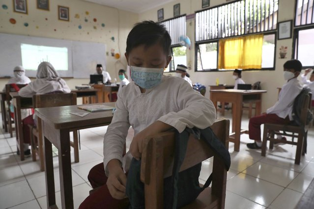 Students wearing face masks sit spaced apart during a trial run of a class with COVID-19 protocols at an elementary school in Jakarta, Indonesia, Friday, June 4, 2021. The world's fourth-most populous country, with about 275 million people, has reported more coronavirus cases than any other Southeast Asian country. (Photo by Tatan Syuflana/AP Photo)