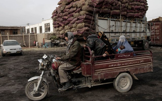 Afghan family goes away on a motocarreta after buying coal at a shop near Kabul, on November 3, 2013. The coal price of firewood has risen in the region with winter looming. (Photo by Rahmat Gul/AP Photo)