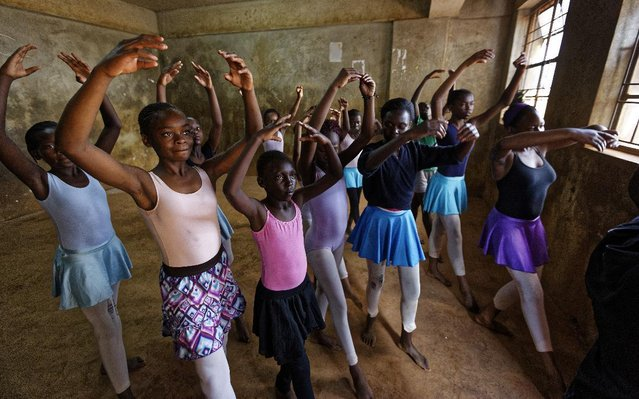 In this photo taken Friday, December 9, 2016, young ballerinas receive instruction from Kenyan ballet dancer Joel Kioko, 16, in a room at a school in the Kibera slum of Nairobi, Kenya. In a country not usually associated with classical ballet, Kenya's most promising young ballet dancer Joel Kioko has come home for Christmas from his training in the United States, to dance a solo in The Nutcracker and teach holiday classes to aspiring dancers in Kibera, the Kenyan capital's largest slum. (Photo by Ben Curtis/AP Photo)
