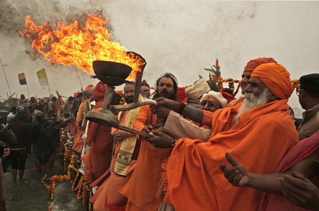 Hindu holy men or Sadhus pray at the Sangam, confluence of rivers Ganges, Yamuna and the mythical Saraswati, during the start of preparations and safe and successful completion of Ardh Kumbh mela, in Allahabad, Monday, December 26, 2016. Ardh Kumbh mela, where millions of Hindu devotees take part and falls after every six years will be held at Allahabad in 2019. (Photo by Rajesh Kumar Singh/AP Photo)