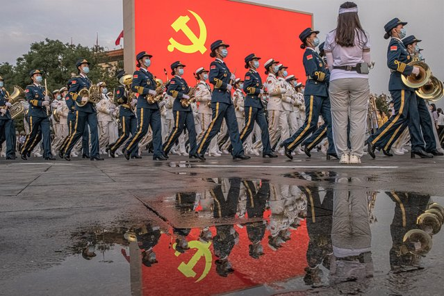Members of the Chinese military orchestra march past a screen showing the Chinese Communist flag on Tiananmen Square before a celebration marking the 100th founding anniversary of the Chinese Communist Party, in Beijing, China, 01 July 2021. China celebrates on 01 July the 100th anniversary of the founding of the ruling Chinese Communist Party. (Photo by Roman Pilipey/EPA/EFE)