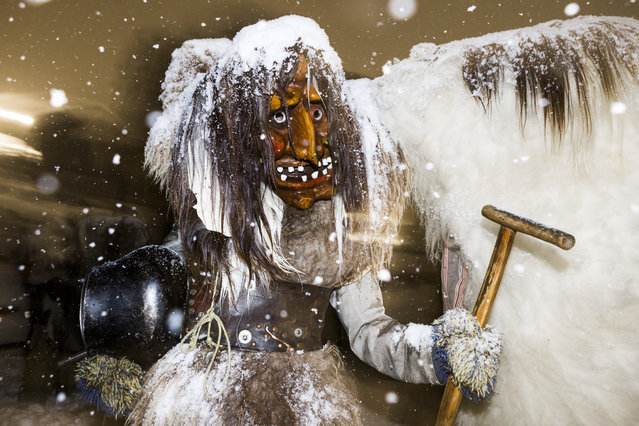 In this February 4, 2016 picture  a masked participant of the traditional carnival  parade poses in the streets of the village of Kippel in the Loetschental valley, southwestern part of Switzerland. During this sinister carnival,  participants wearing  wooden masks and animal furs,  crowd the streets of the villages to scare the people.  (Photo by Dominic Steinmann/Keystone via AP Photo)