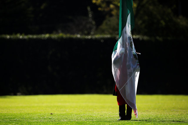 A military cadet is silhouetted while holding a Mexican flag during a troop review by Mexico's new President Andres Manuel Lopez Obrador at Campo Marte in Mexico City, Mexico December 2, 2018. (Photo by Daniel Becerril/Reuters)
