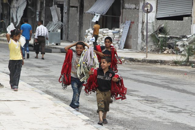 Boys carry ropes for sale along a street in a rebel-controlled area of Aleppo, Syria, August 30, 2015. (Photo by Abdalrhman Ismail/Reuters)