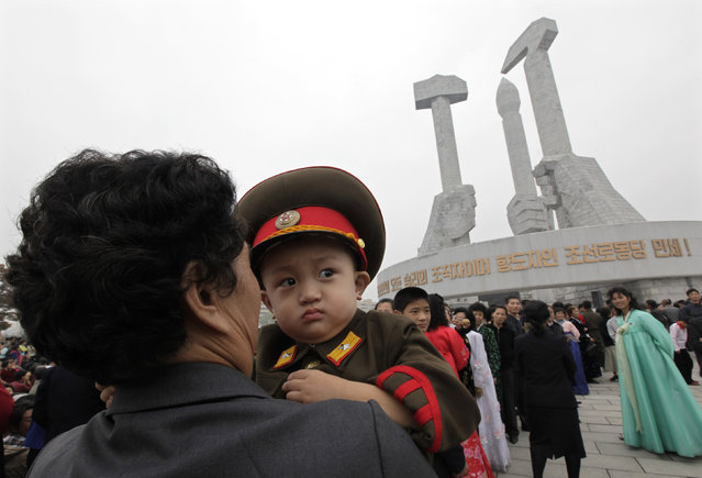 A woman carries a boy dressed in a North Korean army uniform at the Party Foundation Monument in Pyongyang October 11, 2010. (Photo by Petar Kujundzic/Reuters)