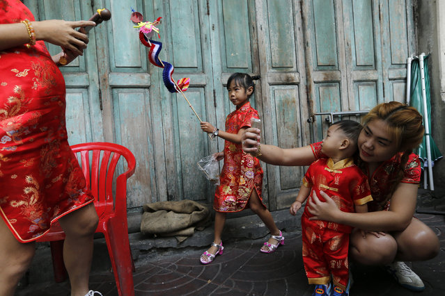 A family dressed in traditional chinese clothes celebrates the Chinese New Year in Chinatown in Bangkok, Thailand February 8, 2016. (Photo by Jorge Silva/Reuters)