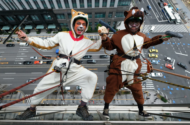 Workers clad in a dog and a wild boar costumes, to represent the outgoing year of the dog and incoming year of the wild boar, clean windows on the side of a hotel in Tokyo on December 13, 2018. (Photo by Kazuhiro Nogi/AFP Photo)