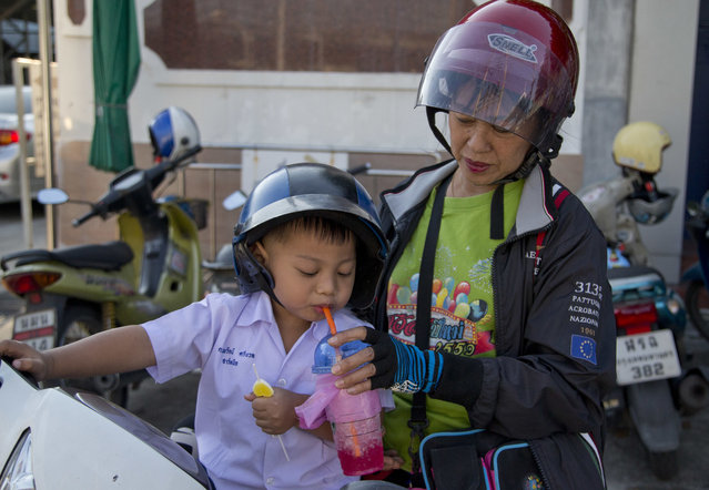 In this Thursday, November 1, 2018, photo, a woman feeds a child with a sweeten fuzzy drink and a candy as she picks him up after school in Bangkok, Thailand. A report by the United Nations Food and Agricultural Organization released Friday says some 486 million people are malnourished in Asia and the Pacific, and progress in alleviating hunger has stalled. More than half of all children who are malnourished live in the region, with stunting that causes long-term damage worsened by food insecurity and inadequate sanitation, even in Bangkok, more than a third of children were not receiving an adequate diet as of 2017, the report said.(Photo by Gemunu Amarasinghe/AP Photo)