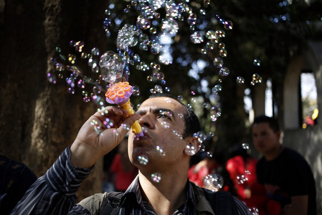 "An Egyptian man blows bubbles at the Giza Zoo, as the country marks Sham el-Nessim, or ""smelling the breeze"", in Giza, Egypt, Monday, April 13, 2015. (Photo by Hassan Ammar/AP Photo)"