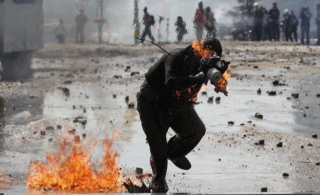 A protestor is on fire after a molotov cocktail goes off during a clash with Turkish riot police at Taksim Square in Istanbul, Turkey, 11 June 2013. (Photo by Sedat Suna/EPA)