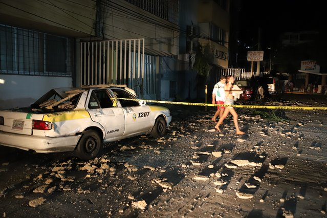 A couple walks past a taxi cab that was damaged by falling debris after a strong earthquake in Acapulco, Mexico, Tuesday, September 7, 2021. The quake struck southern Mexico near the resort of Acapulco, causing buildings to rock and sway in Mexico City nearly 200 miles away. (Photo by Bernardino Hernandez/AP Photo)