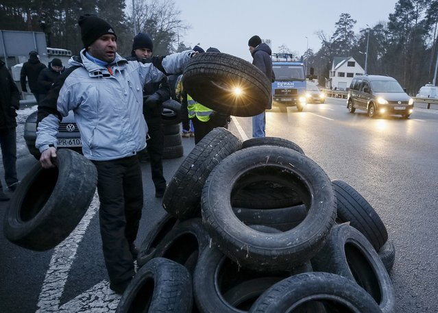 A man places a tyre on a pile during a protest against restrictions on foreign-registered cars which are used by demonstrators to block the traffic in Kiev, Ukraine January 24, 2017. (Photo by Gleb Garanich/Reuters)