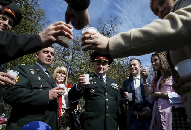 Ukrainian army officers and their relatives drink champagne after a graduation ceremony at the National University of Defence of Ukraine in Kiev, Ukraine April 24, 2015. (Photo by Gleb Garanich/Reuters)